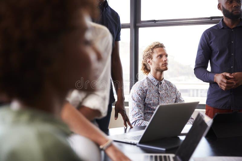 De creatieve bedrijfscollega's die aan presentatie in een vergaderzaal luisteren, sluiten omhoog, selectieve nadruk stock foto's