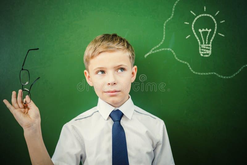 De creatieve en slimme schooljongen heeft een idee bij bord stock fotografie