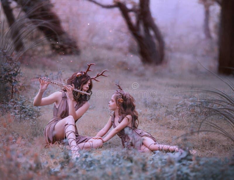 De creatieve fabelachtige familie die, faunmamma speelt wiegeliedje op fluit voor haar kind, fairytale karaktersherten in lang sc royalty-vrije stock foto's