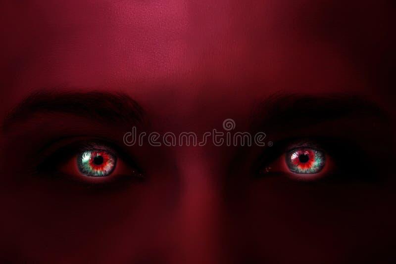De creatieve foto van het gezicht van een vrouw met neonlicht donkerrode kleur en de gloeiende multi-colored ogen met geheimzinni stock afbeelding