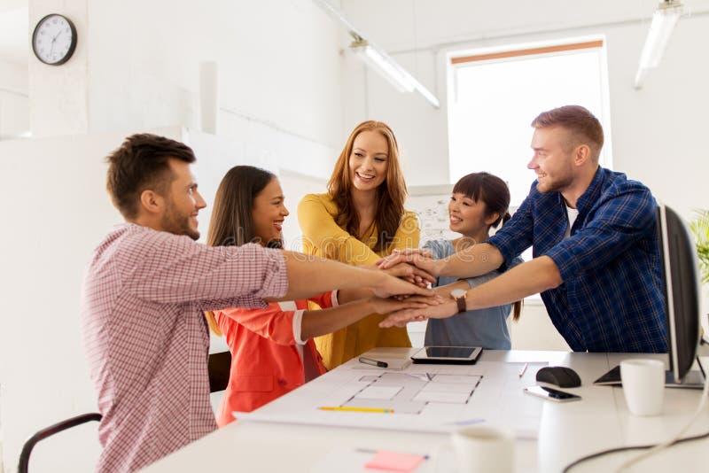 De creatieve handen van de teamholding samen op kantoor stock afbeeldingen