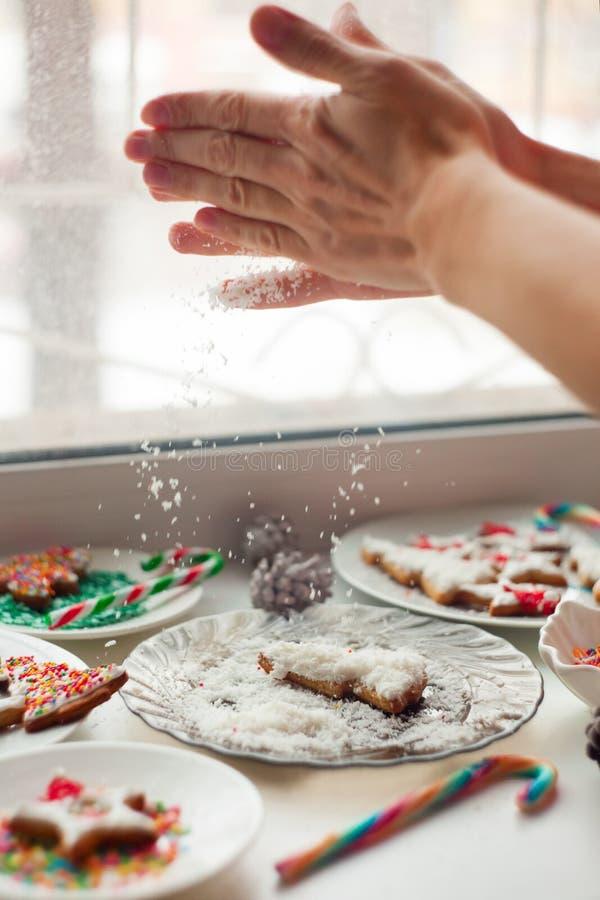 De creatieve Kerstmiskoekjes op de witte plaat, handen bestrooien crumbs, concept nieuw jaar en chrismassnoepjes, gebakken vakant stock fotografie