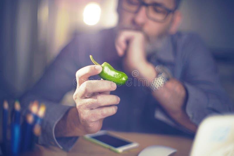 De creatieve ontwerper bekijkt groene paprika, hete Spaanse peperpeper royalty-vrije stock foto's