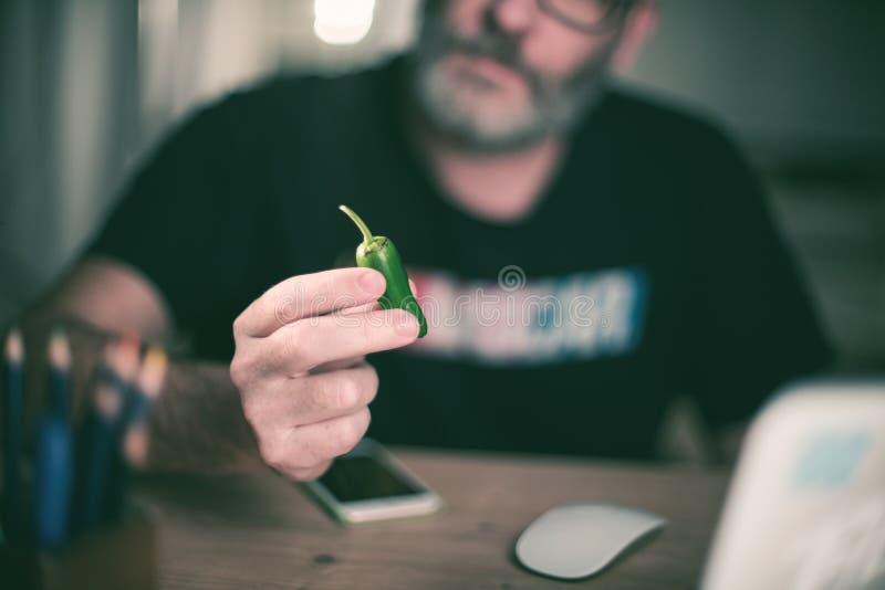 De creatieve ontwerper bekijkt groene paprika, hete Spaanse peperpeper royalty-vrije stock foto