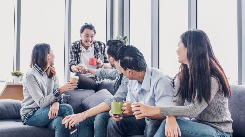 De creatieve ontwerper neemt koffiepauze bij bureaucafetaria de zitting van de multiethnicswerknemer bij bank en het spreken en h royalty-vrije stock afbeelding