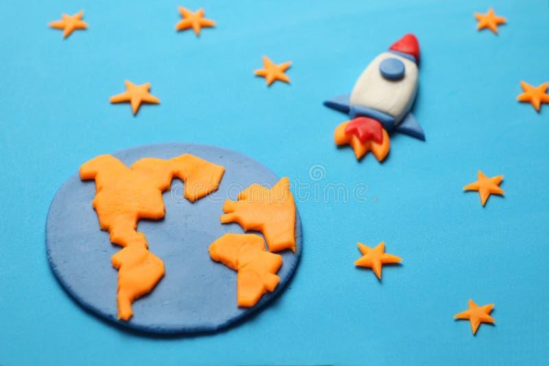 De creatieve raket van de ambachtplasticine in open plek, astronautendromen Sterren, aarde Beeldverhaalart. stock foto