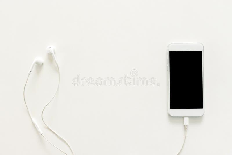 De creatieve vlakte legt foto van werkruimtebureau met oortelefoons en mobiele telefoon met het lege scherm op exemplaar ruimte w stock afbeelding