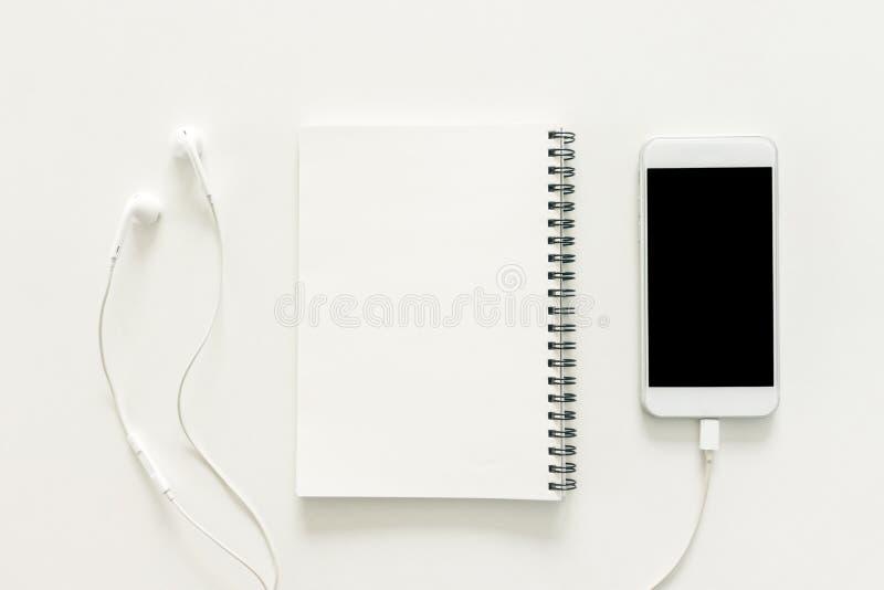 De creatieve vlakte legt foto van werkruimtebureau met sketchbook en mobiele telefoon met het lege scherm op exemplaar ruimte wit stock foto's