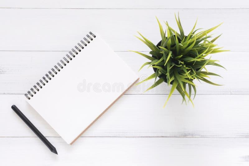 De creatieve vlakte legt foto van werkruimtebureau De witte achtergrond van de bureau houten lijst met open spot op notitieboekje stock fotografie
