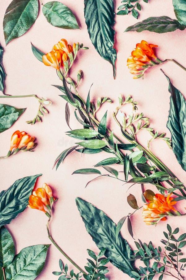 De creatieve vlakte legt gemaakt van tropische bloemen en bladeren op pastelkleur roze achtergrond royalty-vrije stock afbeeldingen