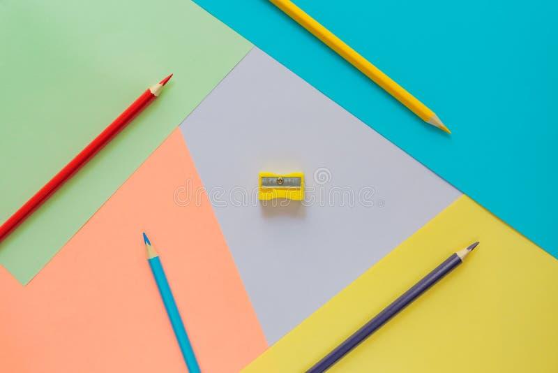 De creatieve vlakte legt met school suppllies multicolored potloden en slijper op pastelkleur kleurrijke achtergrond Terug naar S royalty-vrije stock foto