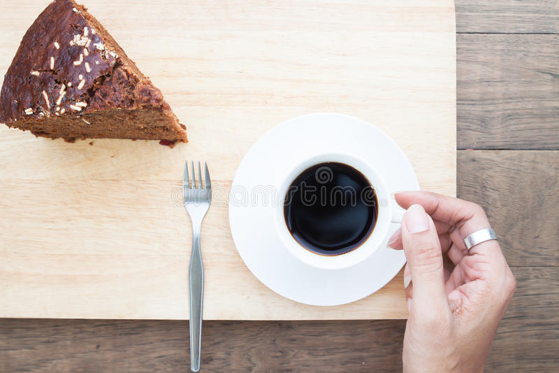 De creatieve vlakte legt van vrouwenhand met koffiekop en chocoladecake stock foto's