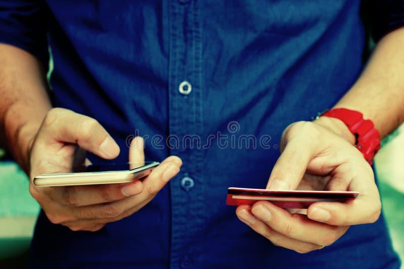 De creditcard van de jonge mensenholding en het gebruiken van slimme telefoon met het winkelen royalty-vrije stock foto