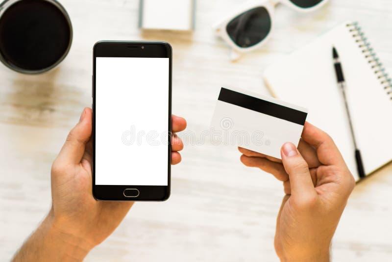 De creditcard van de holdingshand en het gebruiken van smartphone Een zwarte smartphonespot omhoog en een creditcard in de handen stock afbeelding