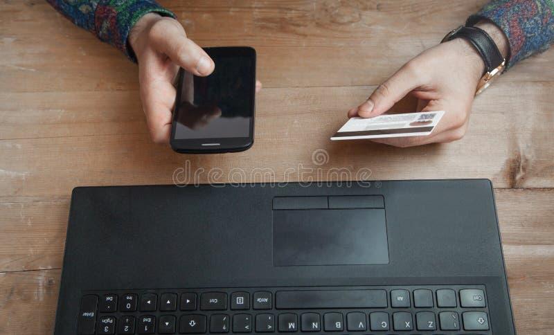 De creditcard van de mensenholding en het gebruiken van telefoon stock foto's