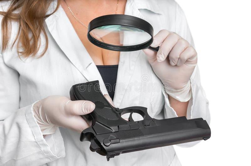 De criminologiedeskundige die pistool bekijken en verzamelt bewijsmateriaal royalty-vrije stock foto's