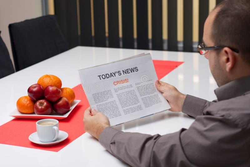 De crisisartikel van de mensenlezing in een krant stock fotografie