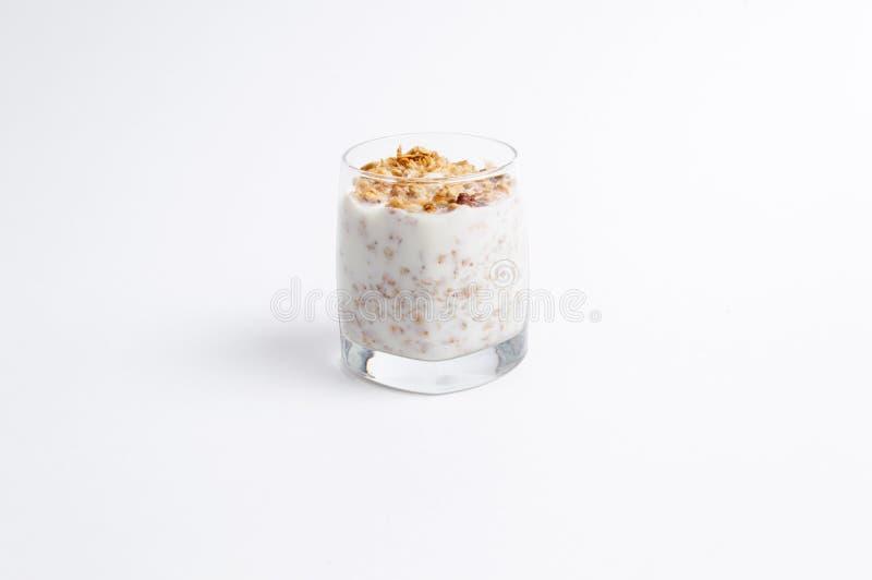 De cristal por completo de muesli y de la leche en un fondo blanco imágenes de archivo libres de regalías