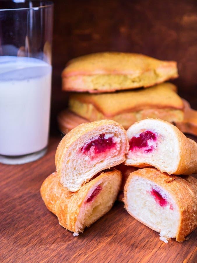 De croissantkers in een besnoeiing ligt bovenop elkaar, naast de cake en de melk stock foto's