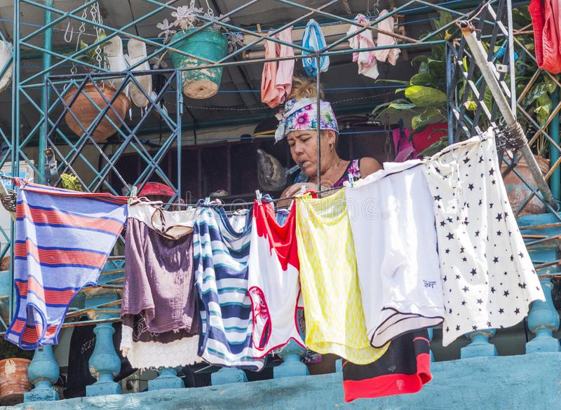 De Cubaanse vrouwen uit haar wasserij hangt op haar balkon in Havana Cuba te drogen stock foto