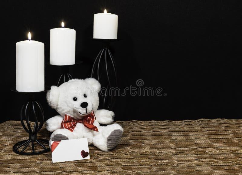 De Cudlelyteddybeer met rode vlinderdas, witte kaarsen streek op zwarte kaarshouders neer op netwerkonderleggertje en houten lijs royalty-vrije stock fotografie
