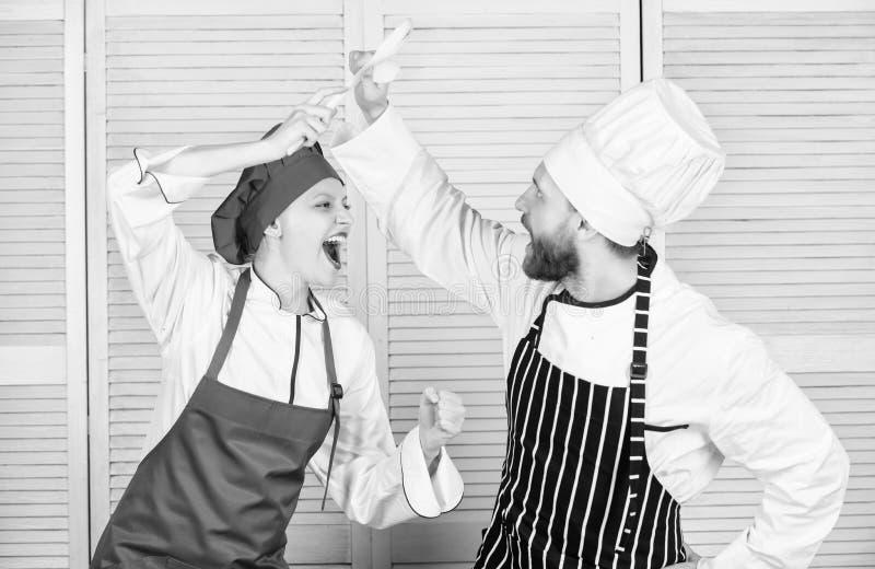 De culinaire vrouw en de gebaarde man tonen concurrenten Uiteindelijke het koken uitdaging Culinaire slag van twee chef-koks Paar royalty-vrije stock afbeeldingen