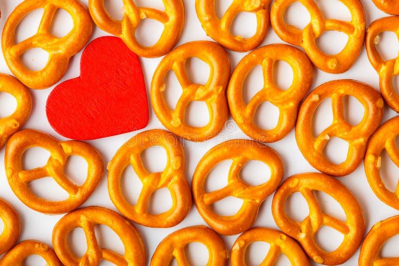 De dag van achtergrond Valentine pretzelspatroon en rood hart. royalty-vrije stock afbeeldingen