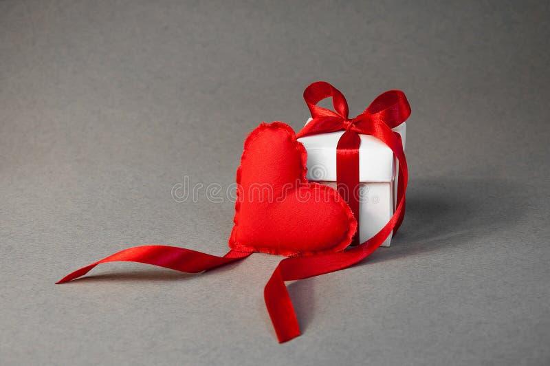 de Dag van conceptenvalentine ` s Klein Zacht Rood Toy Heart en Witte Giftdoos met Rood Lint op Grey Background royalty-vrije stock afbeeldingen