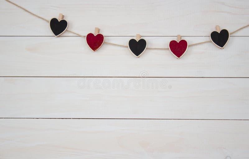 De dag van de valentijnskaart `s Harten hangin op natuurlijk koord Houten witte achtergrond Retro stijl royalty-vrije stock afbeeldingen
