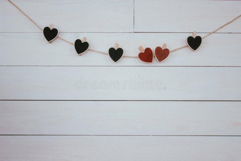 De dag van de valentijnskaart `s Rode en zwarte harten hangin op natuurlijk koord Houten witte achtergrond Retro stijl royalty-vrije stock afbeelding