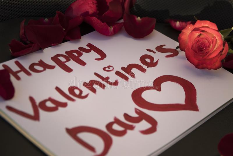 De Dag van gelukkig die Valentine in rode lippenstift rond rode roze bloemblaadjes wordt geschreven en nam toe stock afbeelding