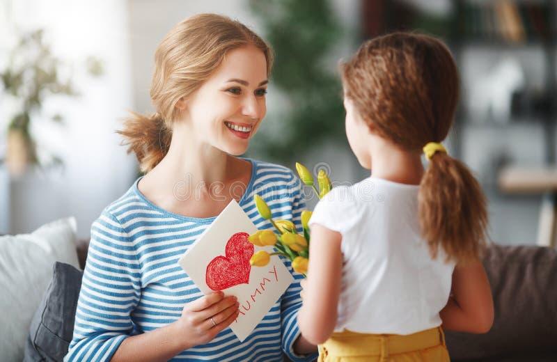 De dag van de gelukkige moeder! De kinddochter wenst mamma's geluk en geeft haar een prentbriefkaar en een gele bloementulp stock foto
