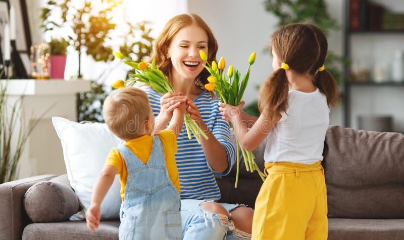 De dag van de gelukkige moeder! De kinderen wenst mamma's geluk en geeft haar een gift en bloemen royalty-vrije stock fotografie