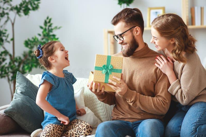 De dag van de gelukkige vader! de het familiemamma en dochter wensen papa geluk en geven gift royalty-vrije stock afbeelding
