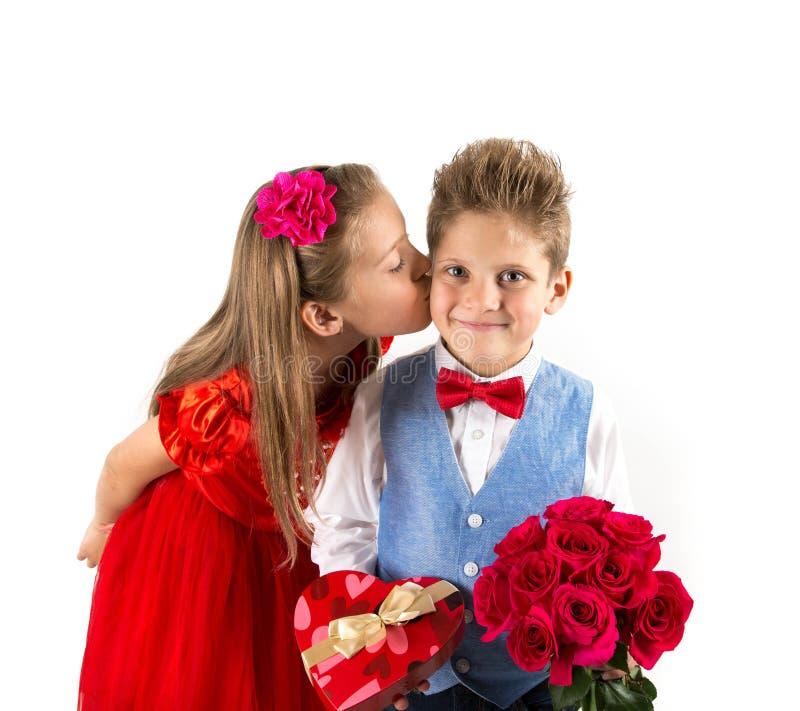 De Dag van heilige Valentine ` s Mooi meisje met rode kleding en herenjongen met blauw vest, rood vlinderdasje, rood rozenemmer e stock afbeeldingen