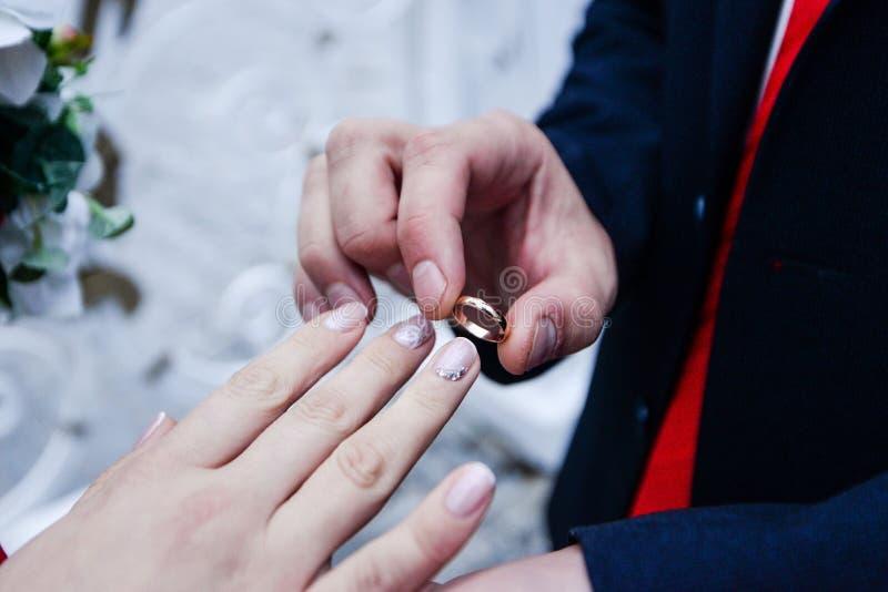 De dag van het huwelijk De bruidegom plaatst de ring op de bruid` s hand De close-up van de foto royalty-vrije stock afbeeldingen