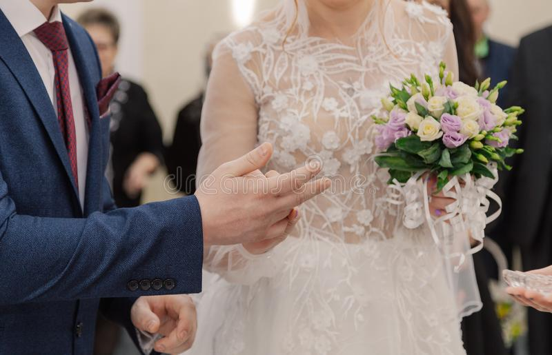De dag van het huwelijk De bruidegom plaatst de ring op de bruid` s hand De close-up van de foto stock afbeelding