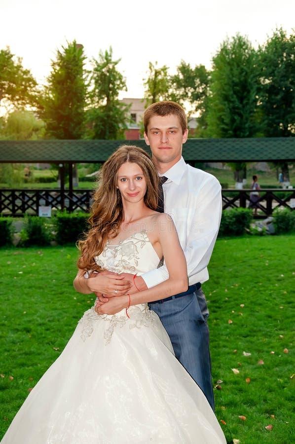De dag van het huwelijk Gelukkig Paar in het Park De gelukkige jonge zakken van de meisjesholding op een witte achtergrond stock foto