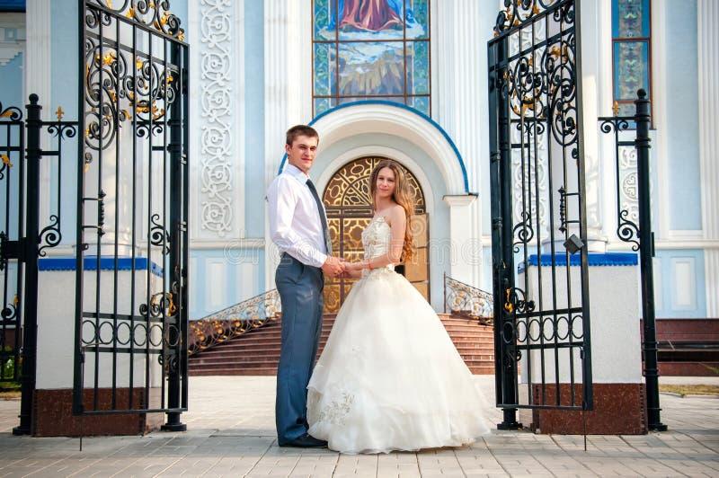 De dag van het huwelijk De gelukkige Bruid van Bruidegomholding hands beautiful voor de Kerk royalty-vrije stock foto