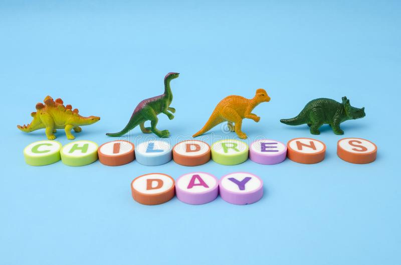 De Dag van kinderen van kleurrijke brieven en plastic dinosaurusspeelgoed dat wordt gemaakt royalty-vrije stock fotografie