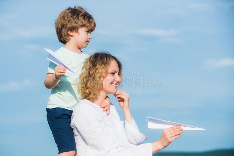 De dag van moeders Leuk houdt weinig jongen document vliegtuig Moeder en zijn zoon die in openlucht spelen royalty-vrije stock fotografie