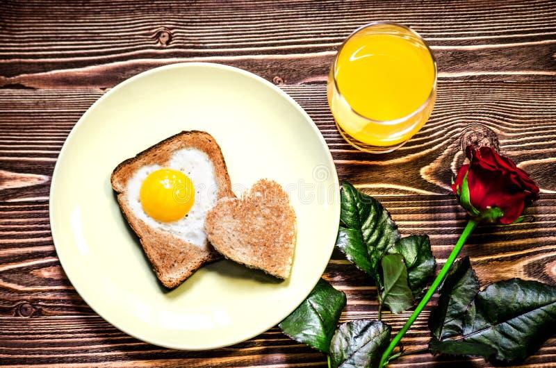 De Dag van ontbijtvalentine ` s Op de plaat is toost met gebraden eieren binnen een hart Daarna op de plaat is wat toost in de vo royalty-vrije stock foto's