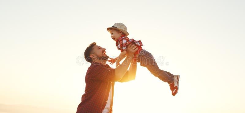De dag van de vader `s Gelukkige familievader en zoon die en op aard bij zonsondergang spelen lachen stock fotografie
