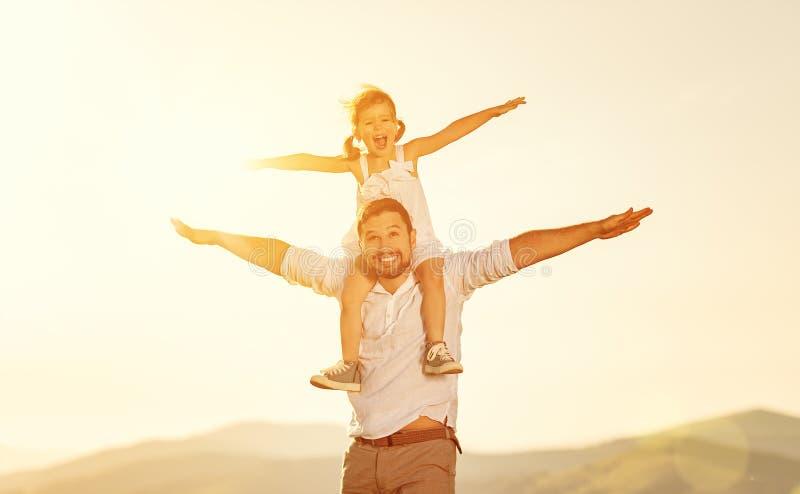 De dag van de vader `s de kinddochter zit in openlucht op haar papaschouders royalty-vrije stock foto's