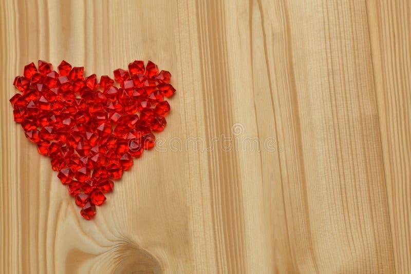 De dag van de valentijnskaart `s Een groot rood plastic die glashart van kleine kristallen wordt gemaakt ligt op een lichte boom royalty-vrije stock foto