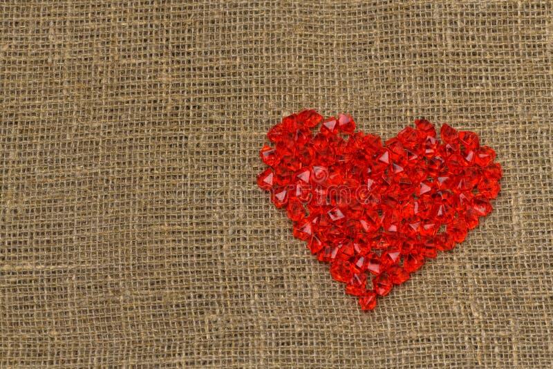 De dag van de valentijnskaart `s Een groot rood plastic glashart van kleine kristallen ligt op een bruine jutezak stock afbeeldingen