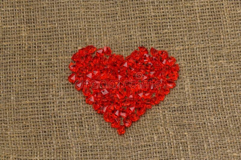 De dag van de valentijnskaart `s Een groot rood plastic glashart van kleine kristallen ligt op een bruine jutezak royalty-vrije stock afbeeldingen