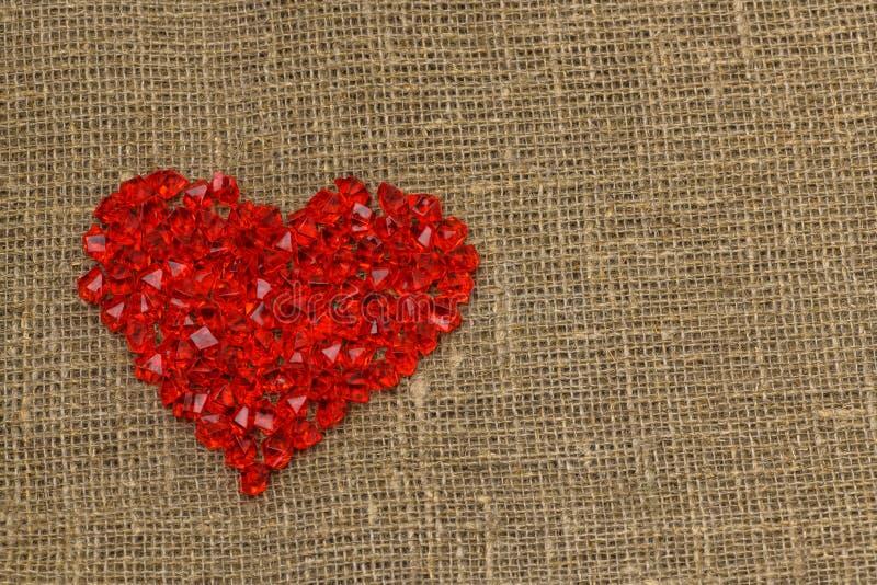 De dag van de valentijnskaart `s Een groot rood plastic glashart van kleine kristallen ligt op een bruine jutezak stock foto's