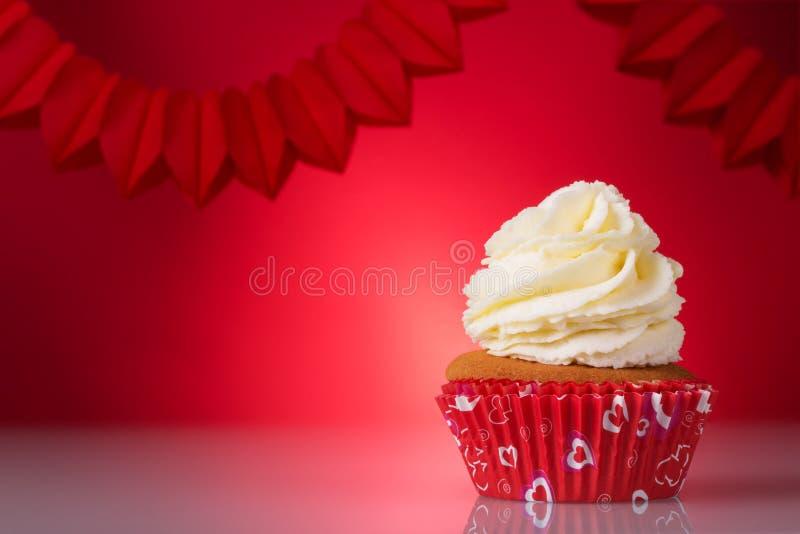 De dag van de valentijnskaart `s Heerlijke cupcakes in rode mand op heldere achtergrond royalty-vrije stock afbeeldingen