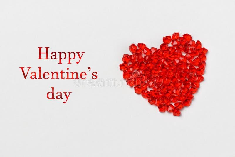De dag van de valentijnskaart `s Het hart van de glas rode kristallen ligt op een grijze achtergrond De dag van ondertekend linke stock foto